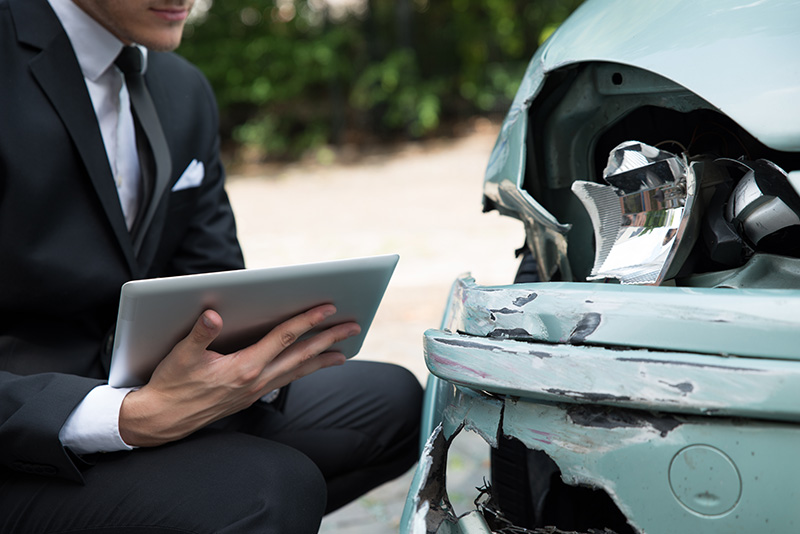 Image of man with a tablet and a damaged car